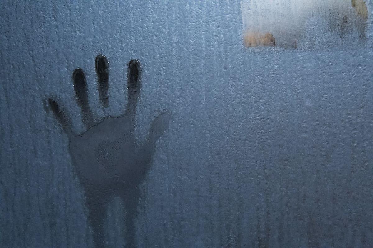 Käden kosketuksen jälki huurteisessa lasiseinässä.
