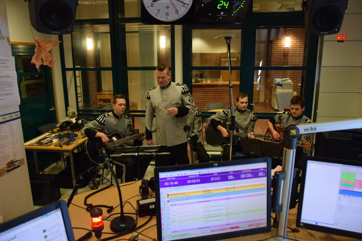 Viisi sotilasasuista soittajaa radion lähetysstudiosa.
