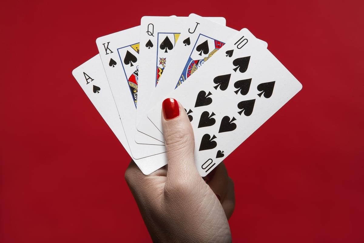Nainen pitää pelikortteja kädessään.