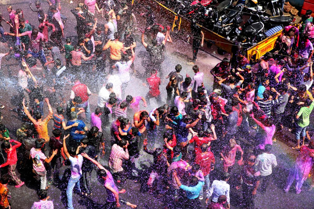 Ihmisjoukko heittää värijauhetta