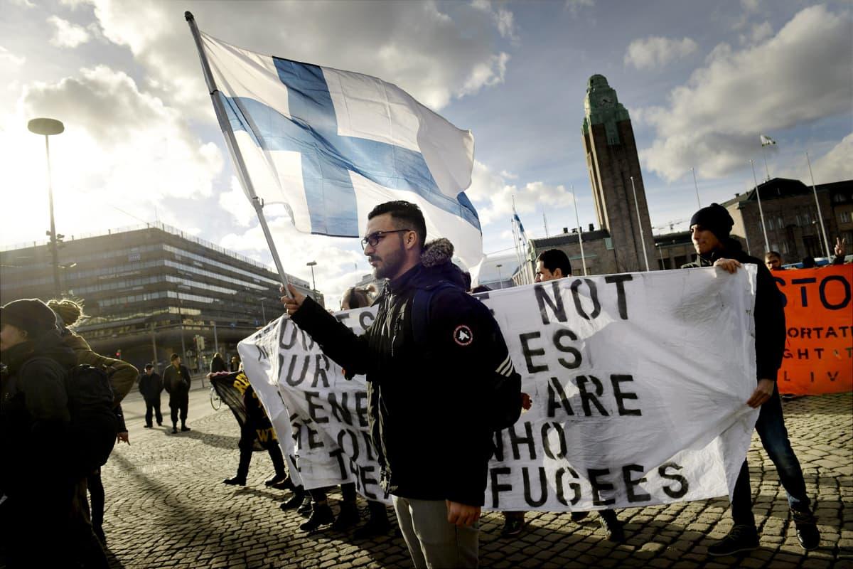 Turvapaikanhakijoita ja heidän mukana mieltään osoittavia Helsingin Rautatientorilla aurinkoisessa kevätsäässä.