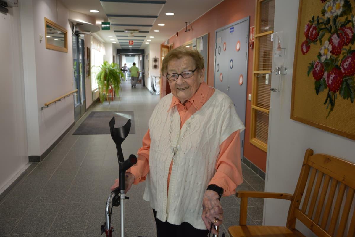 vanha rouva rollaattorin kanssa palvelutalon käytävällä