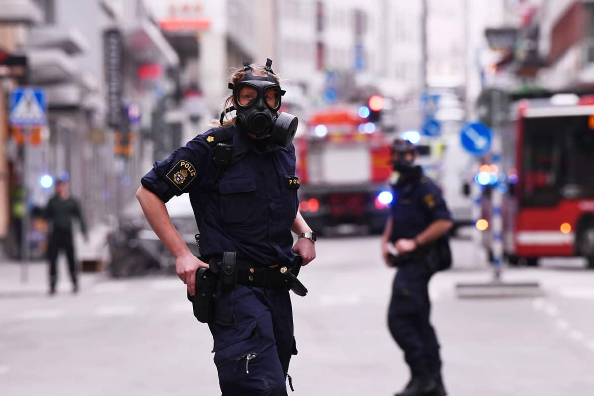 Poliisit vartioivat tavaratalon lähialuetta 7. huhtikuuta Tukholmassa.