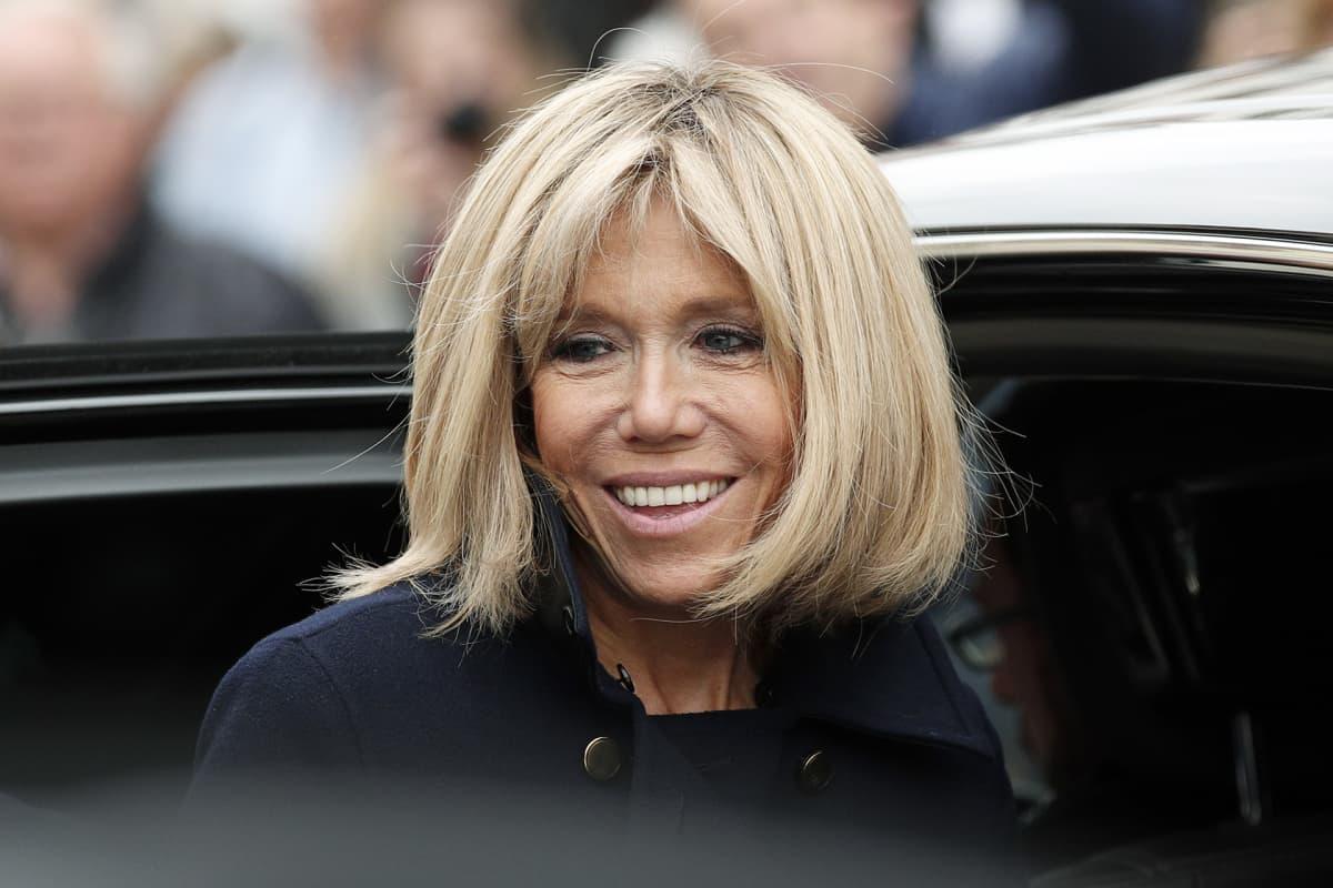 Brigitte Trogneux nousemaassa auton kyytiin hymyillen kameroille.