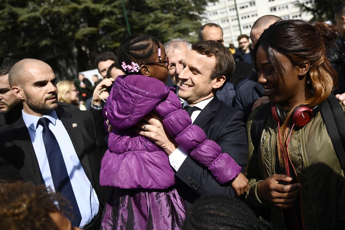 Emmanuel Macron lapsi sylissään kampanjatilaisuudessa
