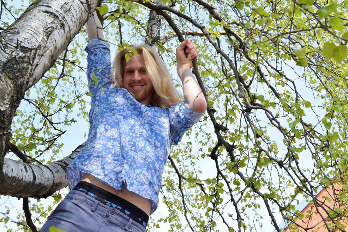 mies roikkuu puussa