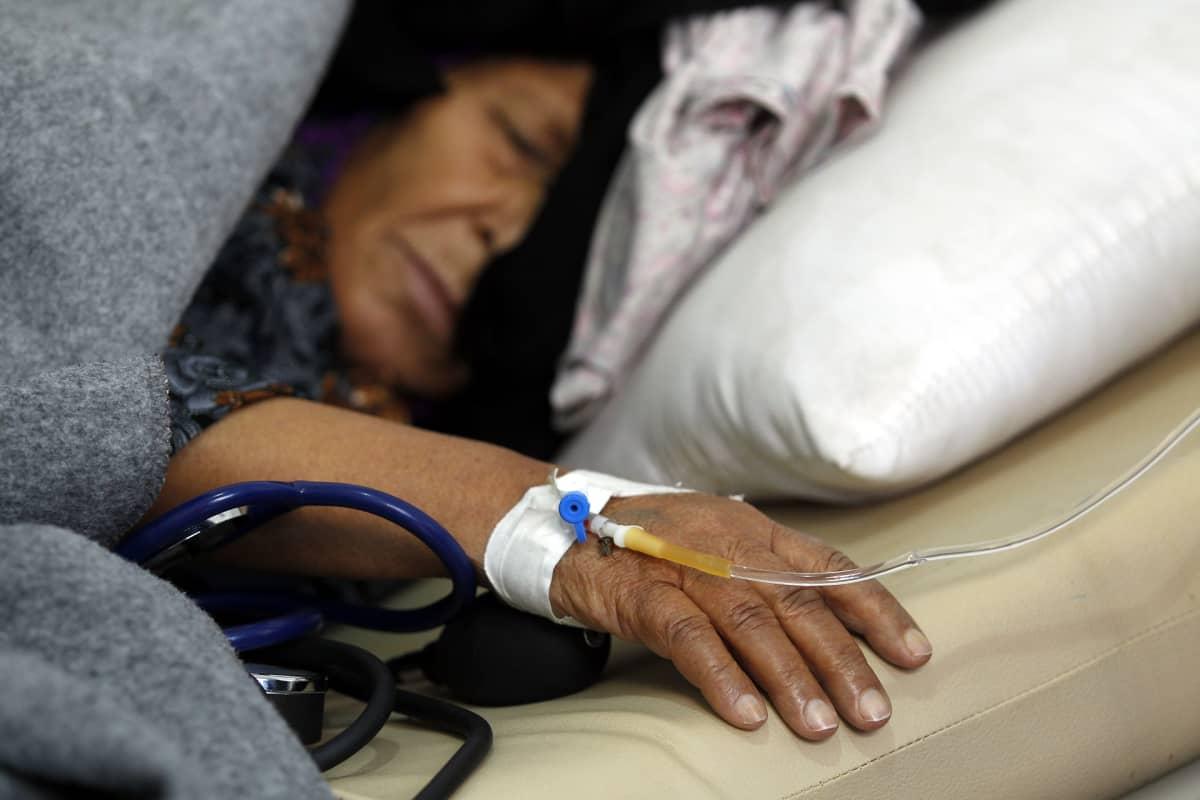Vanhempi nainen nukkuu sairaalasängyssä, hänen käteensä on asetettu tippa.