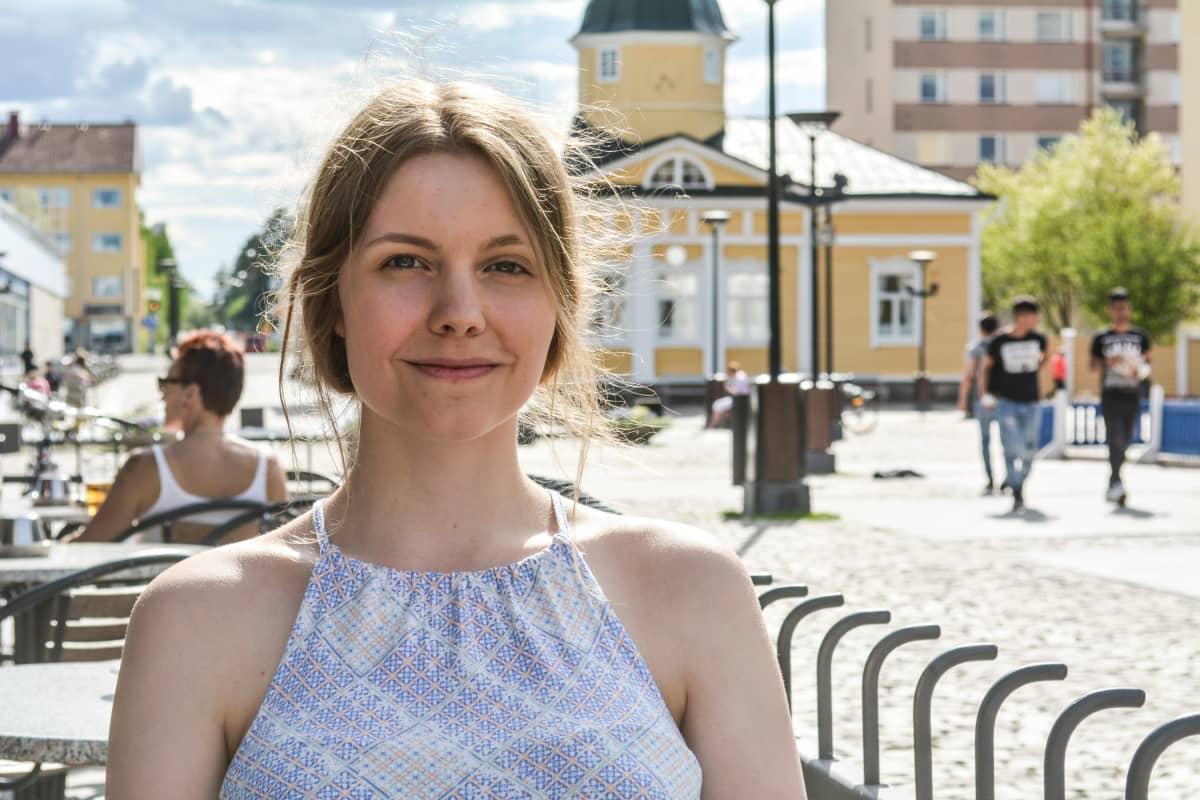 Saara Karjalainen istuu Pitkän Tanelin terassilla. Taustalla Raatintori Kajaanissa.