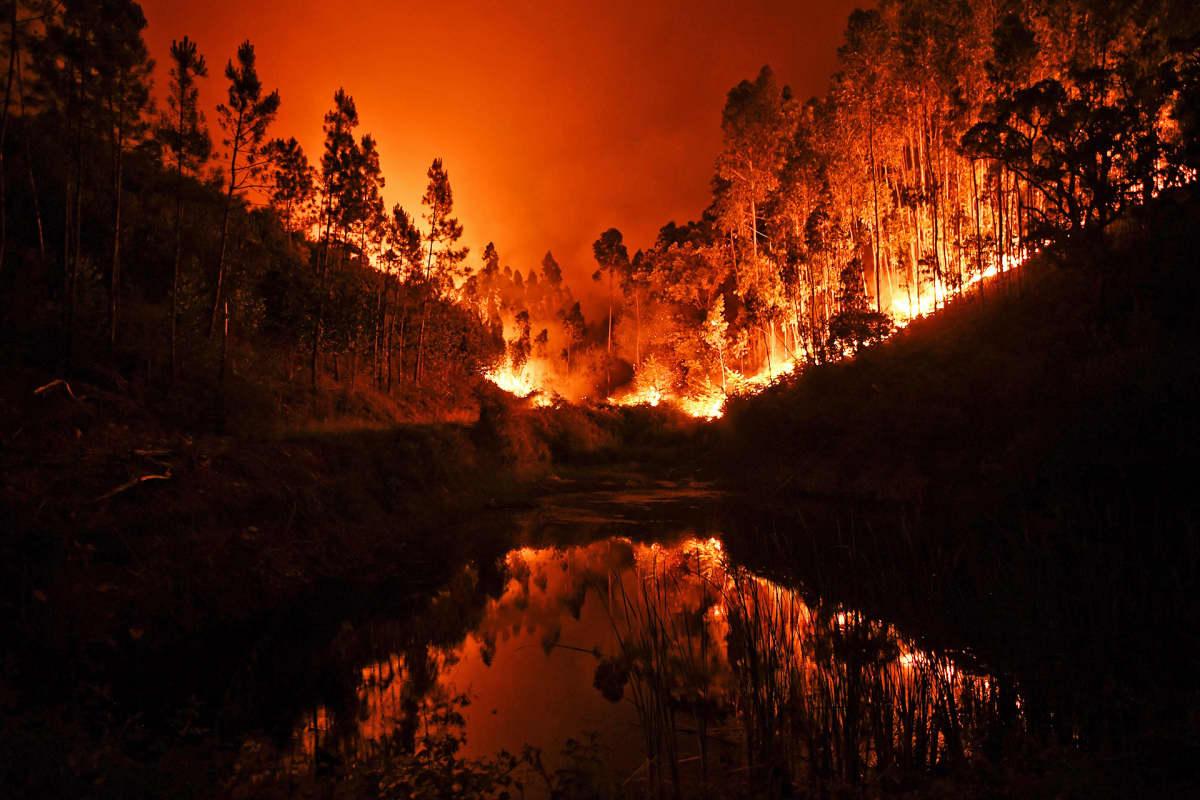 Metsäpalo heijastuu jokeen.