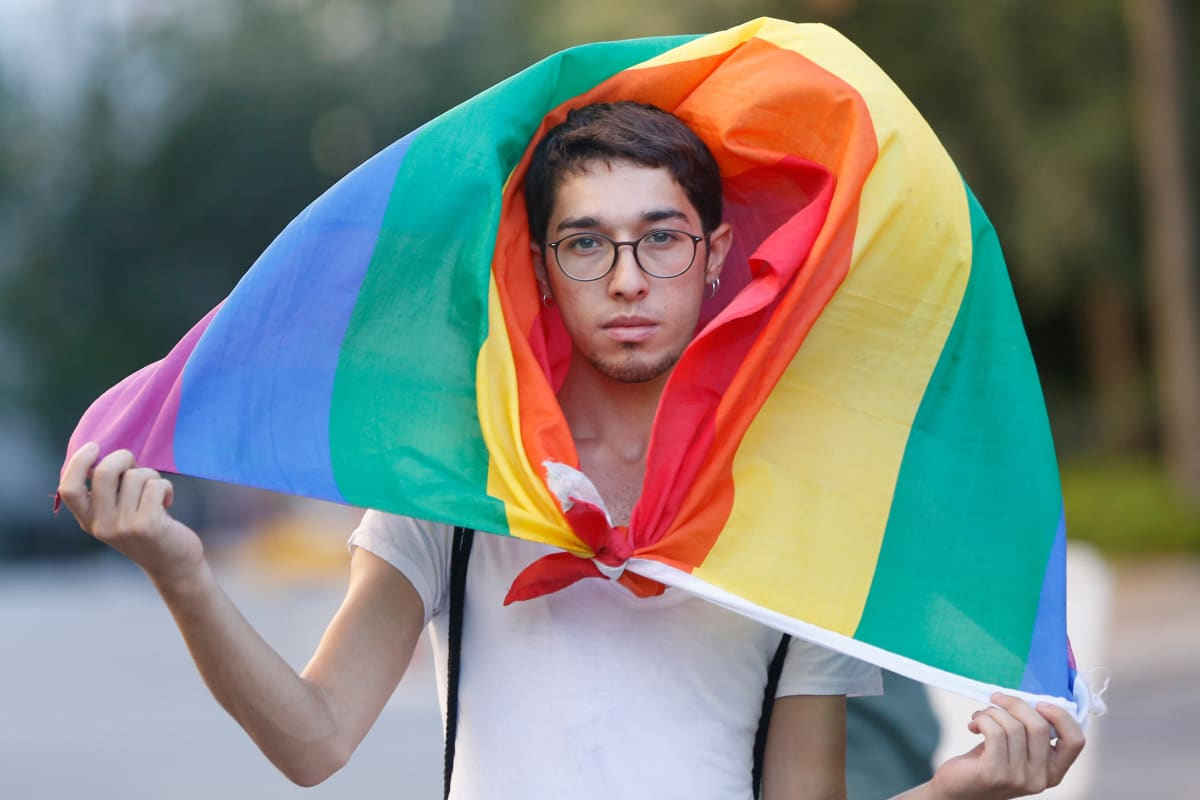 Pride-marssille osallistunut henkilö sateenkaarilipun alla.