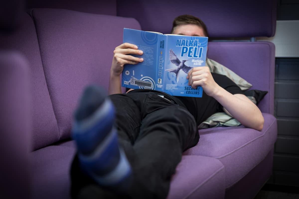 Poika lukee sohvalla.
