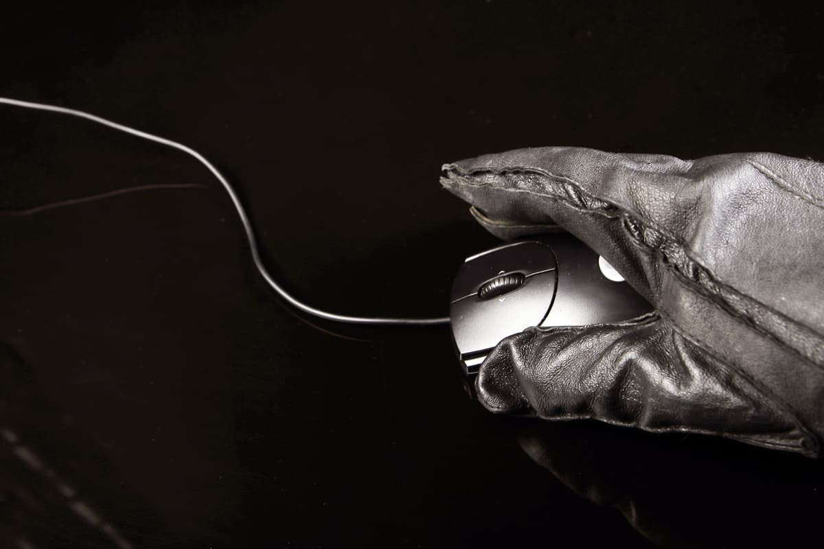 Hanskalla suojattu käsi tietokoneen hiirellä.