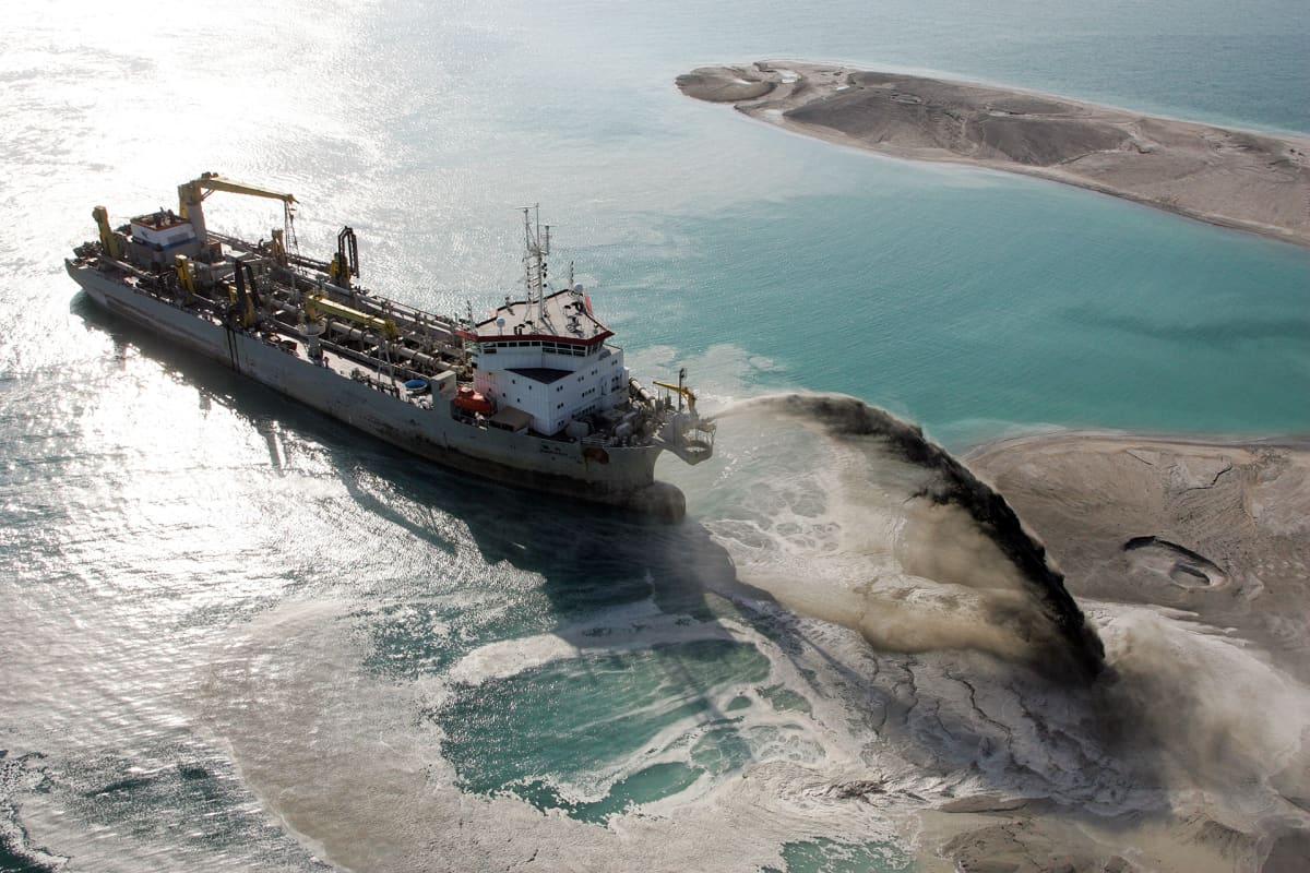 laiva suihkuttaa hiekkaa merestä saareen
