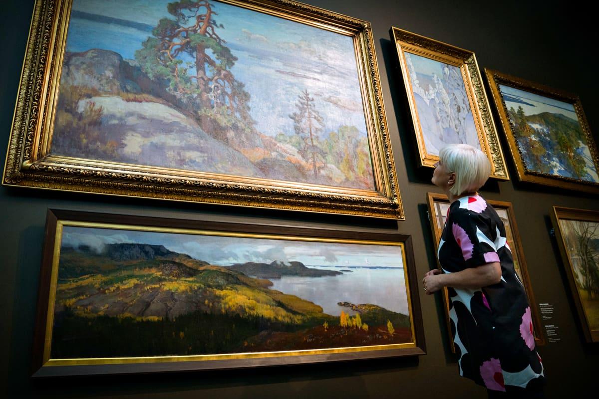 Seija Paasonen katselee klassisia kotimaisia maisemamamaalauksia Ateneumissa.