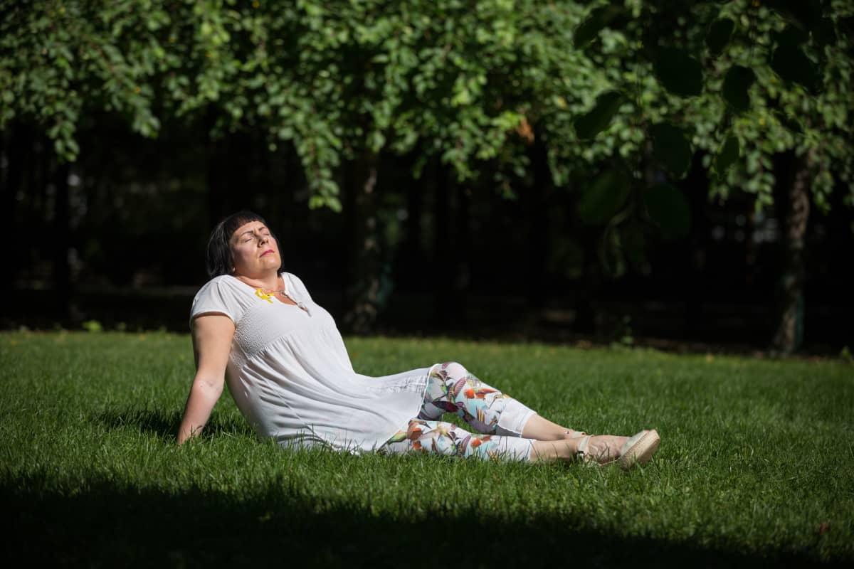 Nainen istuu nurmikolla.