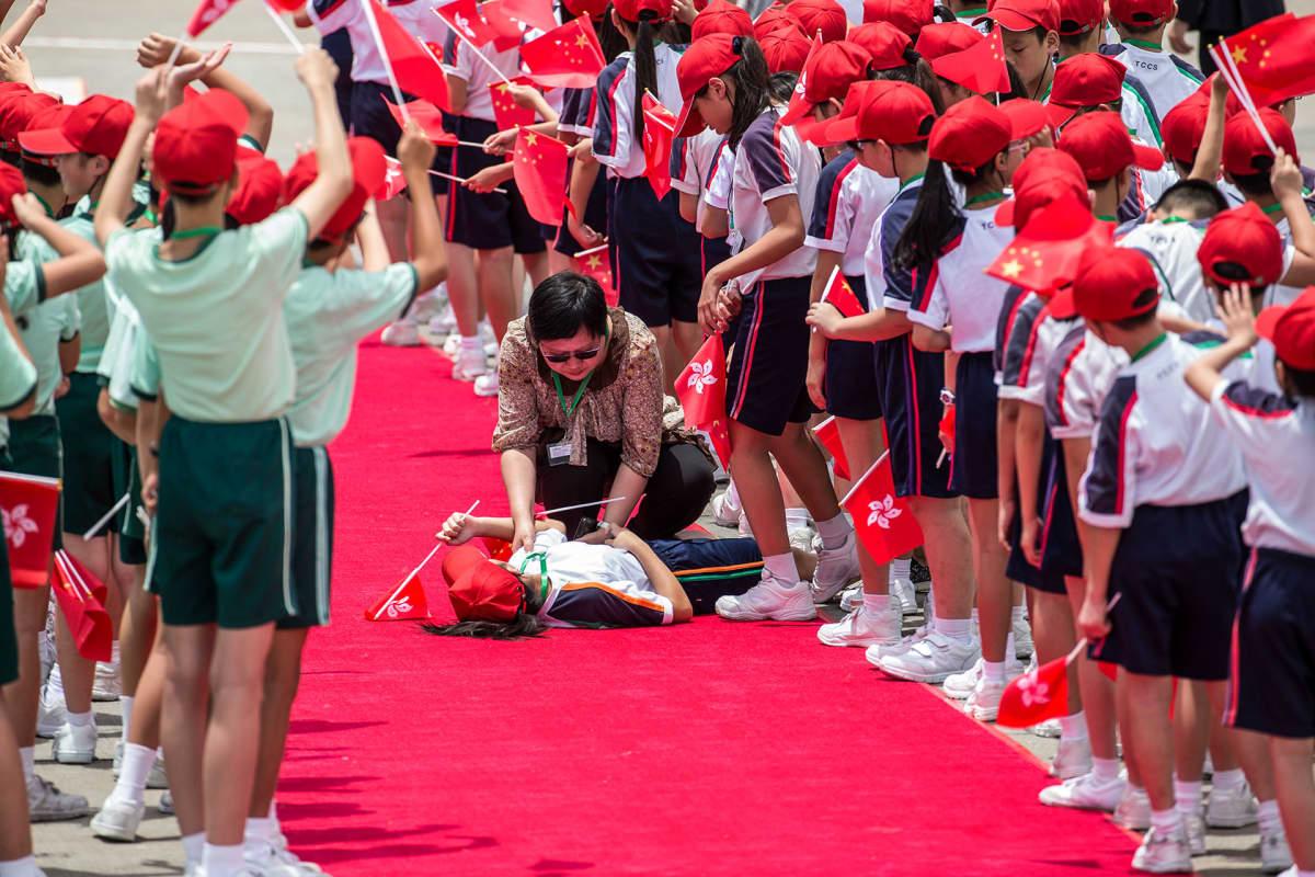 Koululainen makaa tiedottomana menetettyään tajuntansa helteessä. Muut lapset seisovat rivissä.