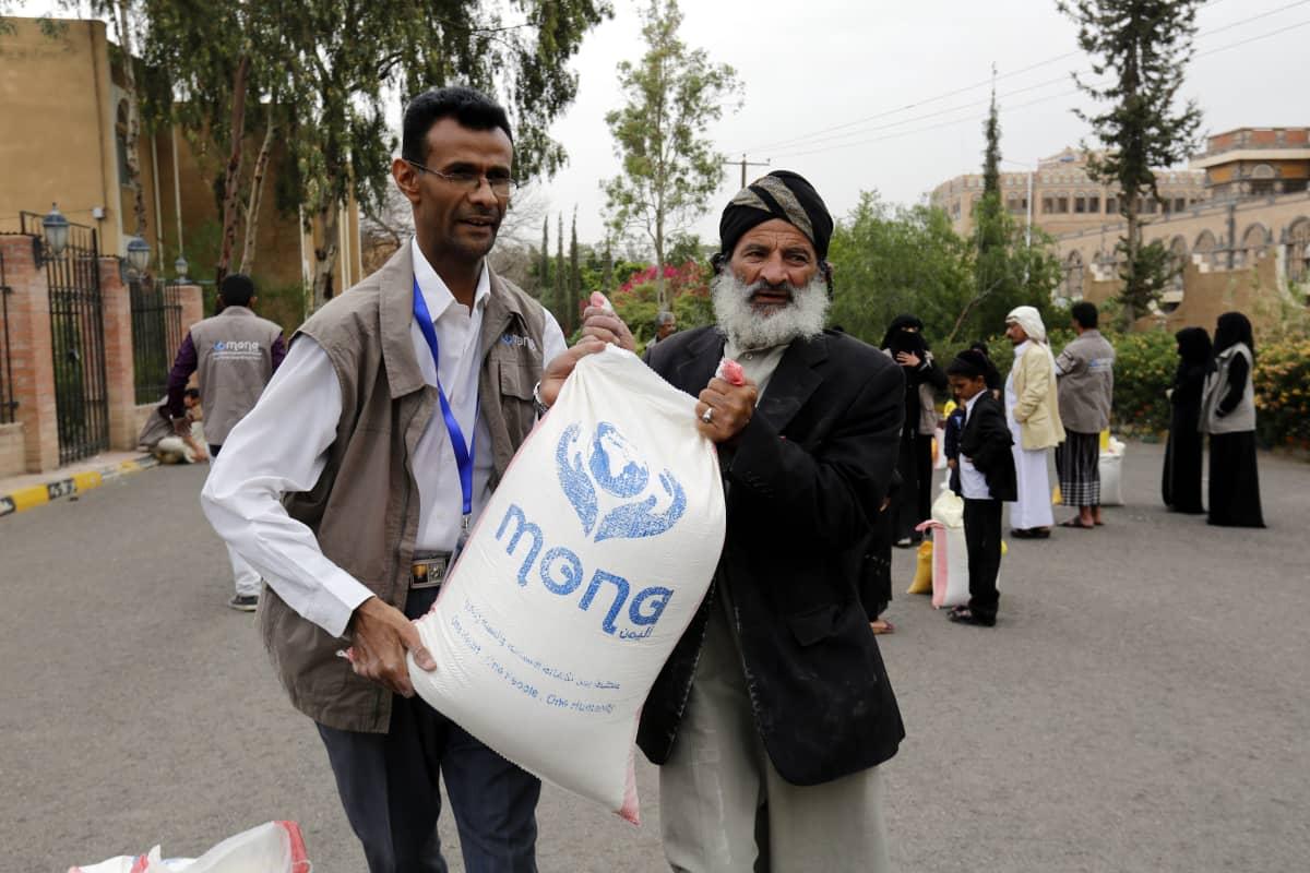 Avustustyöntekijä ja Jemenin juutalaisvähemmistön edustajia kantoivat ruokasäkkiä Sanaassa 30. toukokuuta 2017.