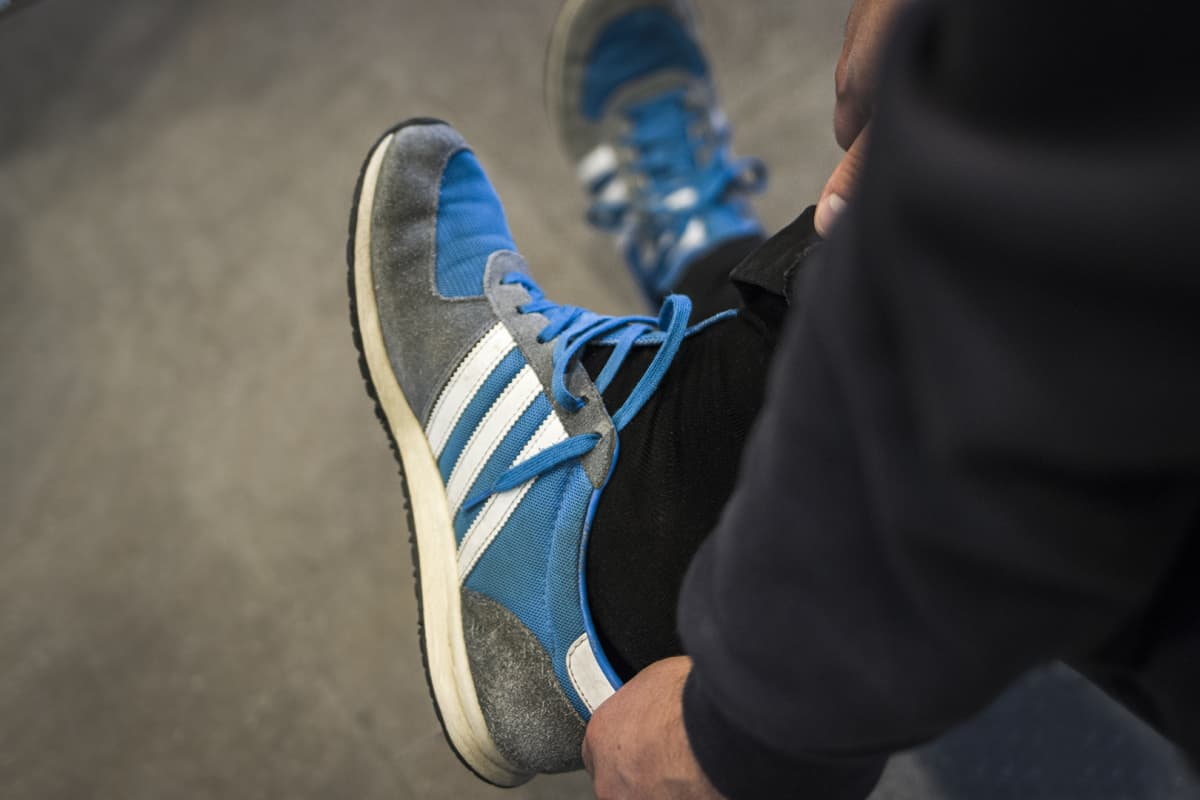 Mies riisuu kenkää jalastaan.