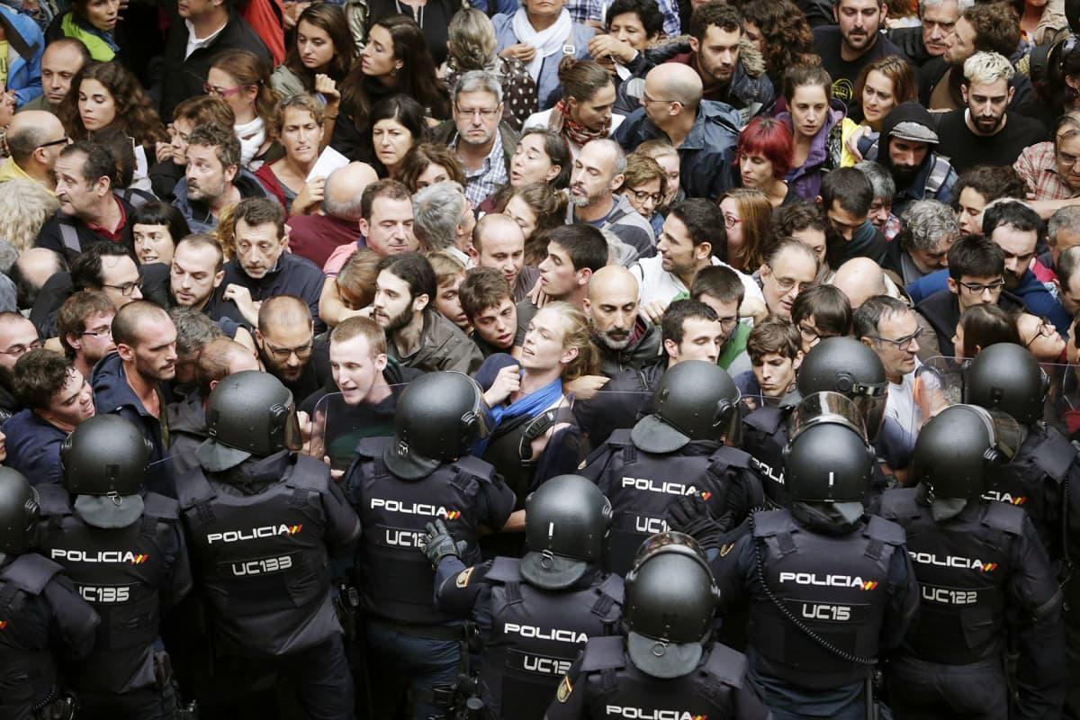 Mellakkapoliisit ja aktivistit ottavat yhteen äänestyspaikkana toimivan koulun edustalla Barcelonassa.