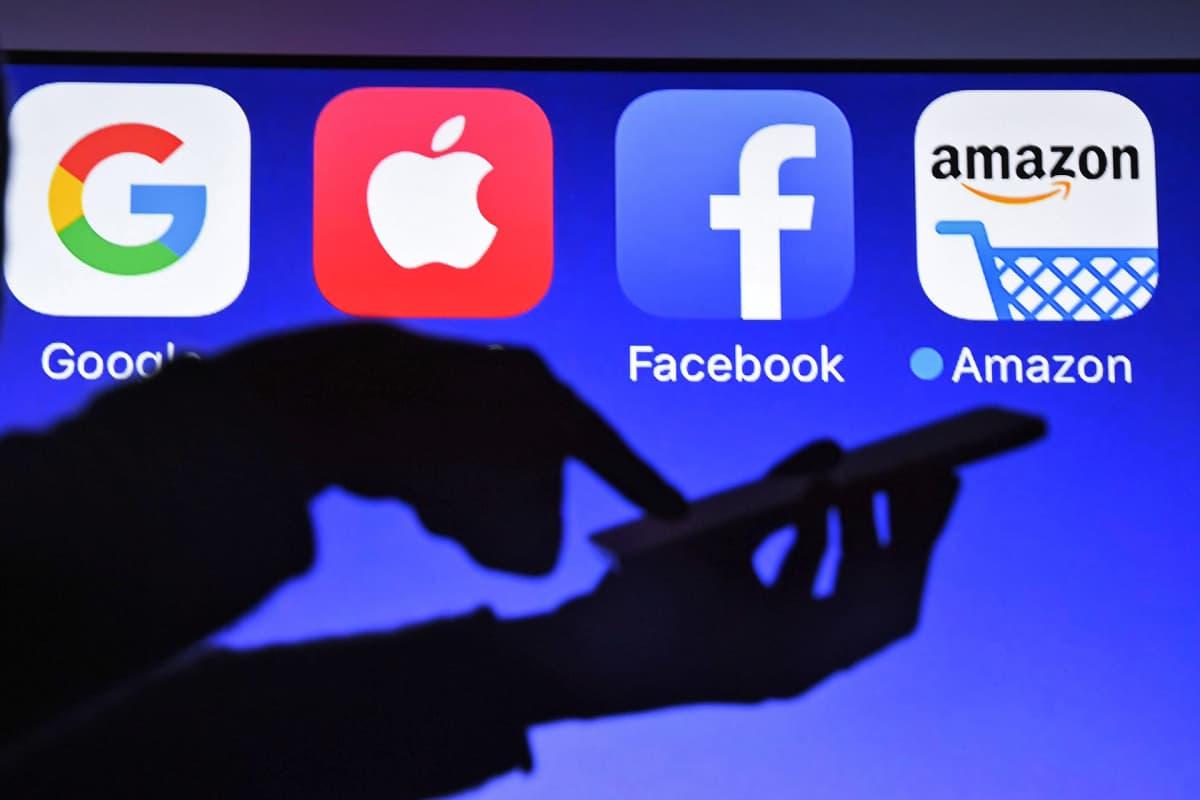 Miehen kädet siluetissa sinistä taustaa vasten. Takana näkyvät Googlen, Applen, Facebookin ja Amazonin logot.