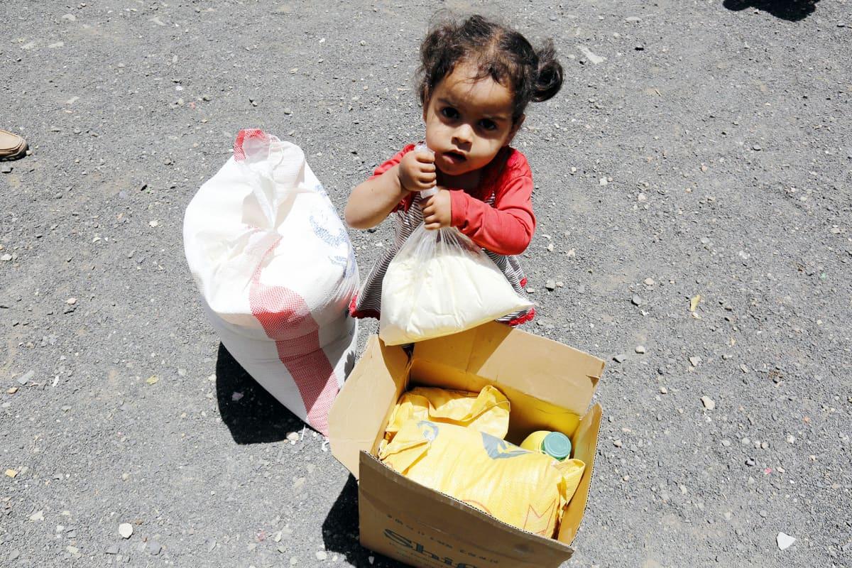 Jemeniläinen lapsi kuvattuna ruokaa sisältävän pahvilaatikon ääressä.