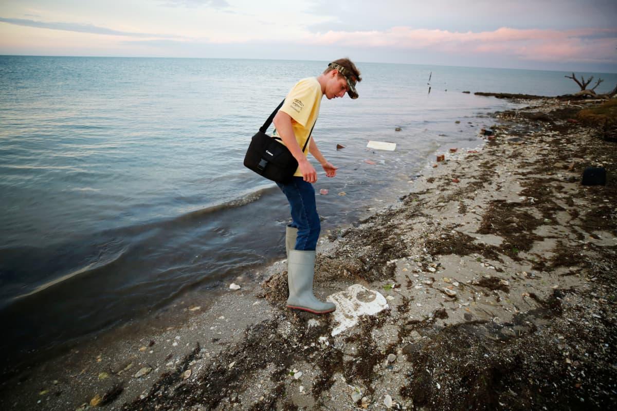 Cameron Evans puhdistaa jalallaan hautakiveä.