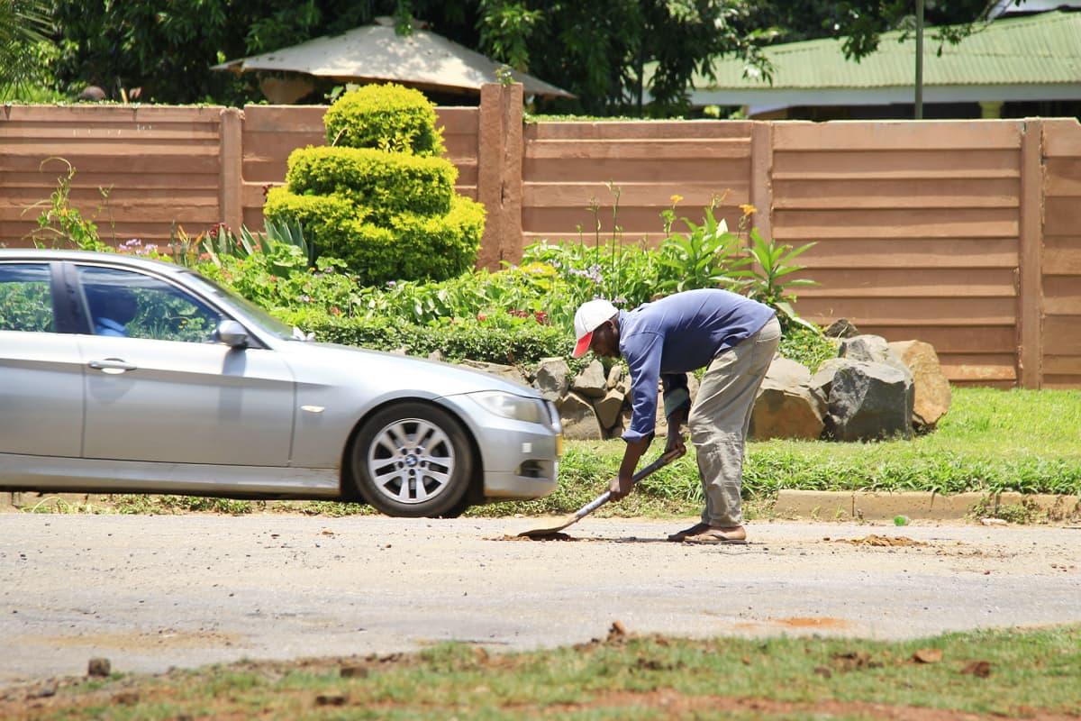 Mies korjaa lapiolla tietä.