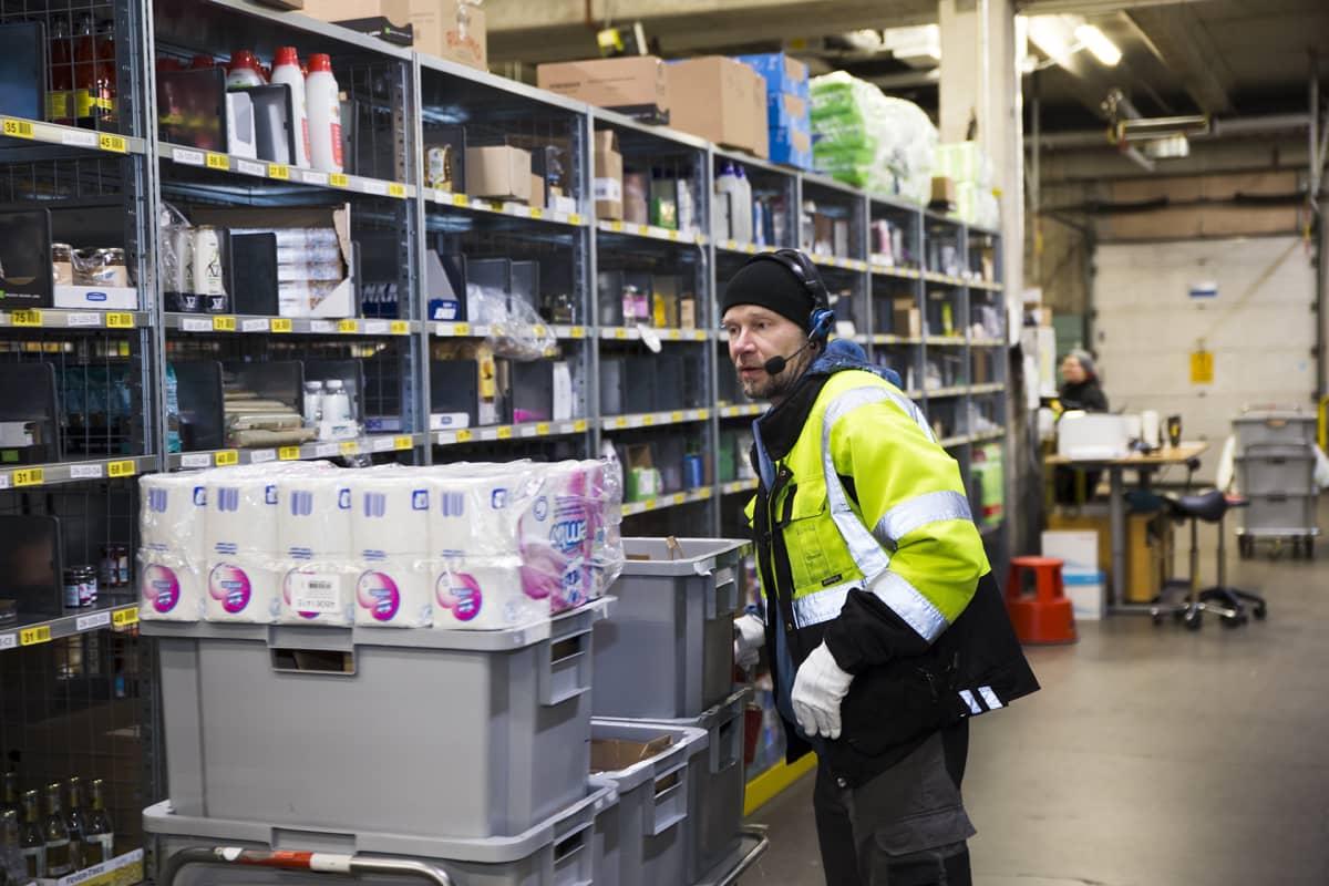 Työntekijä Pasi Rutanen pakkaa verkkokauppaostoksia Kauppahalli 24 logistiikkakeskuksessa Keravalla