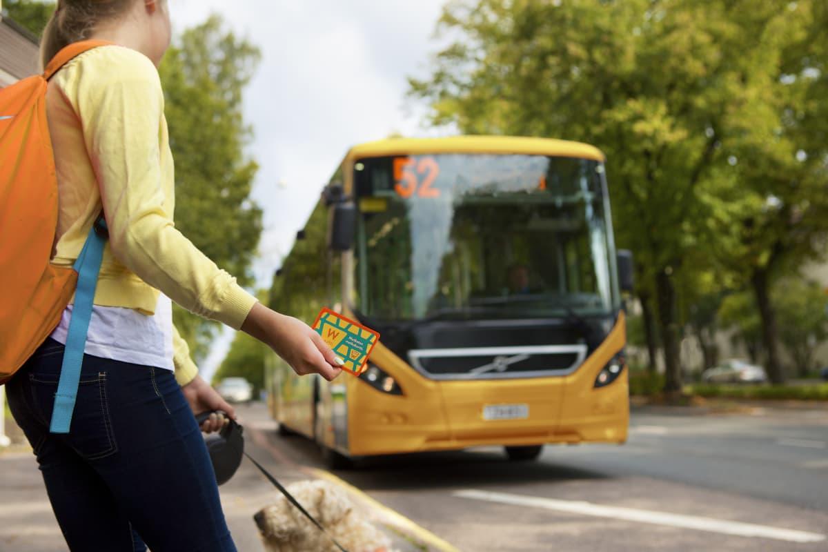 En flicka har ett busskort i handen och väntar på en gul buss som har nummer 52.