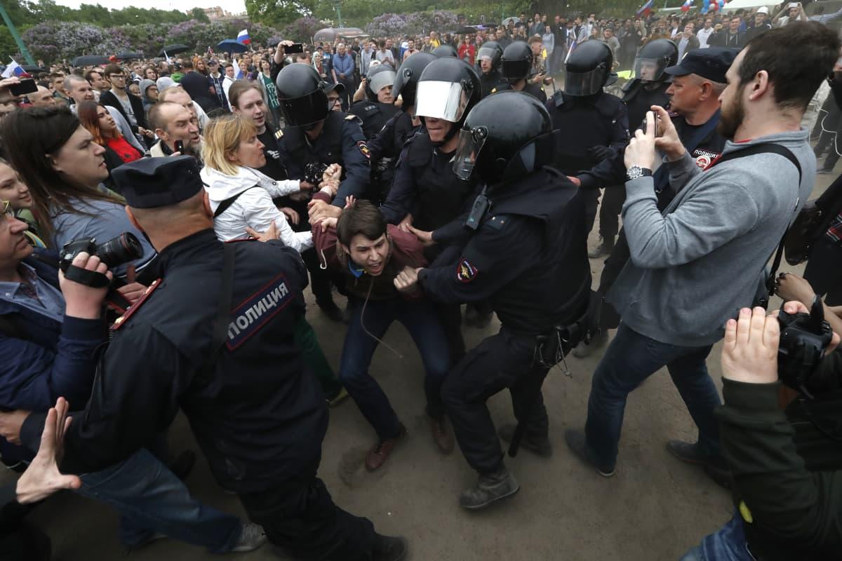 Joukko mellakkapoliisi riepottee nuorta mielenosoittajaa Moskovassa.