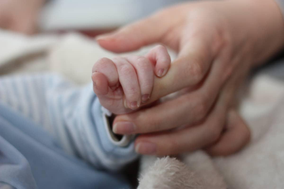 Vauvan käsi äidin kädessä.
