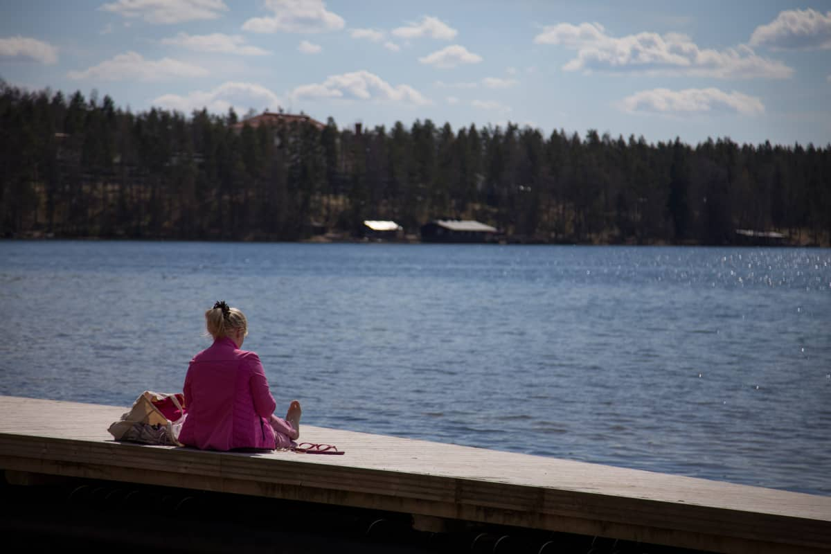 Anonyymi nainen istuu laiturilla aurinkoisella säällä.