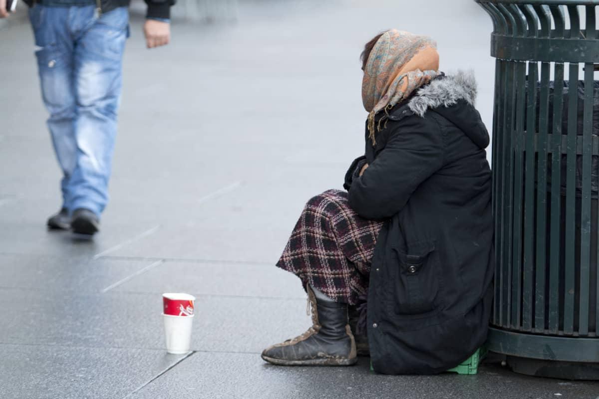 Tiggande kvinna som sitter på huk på gatan.