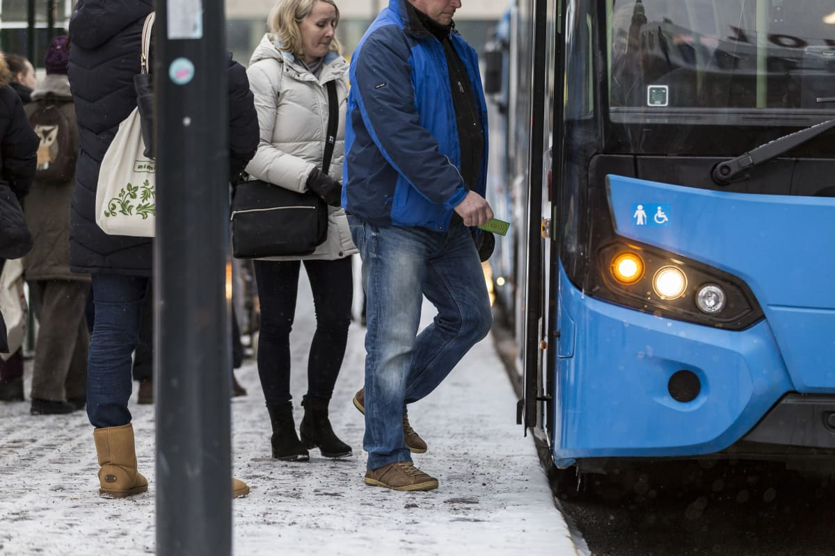 Ihmisiä nousemassa bussin kyytiin Helsingissä.