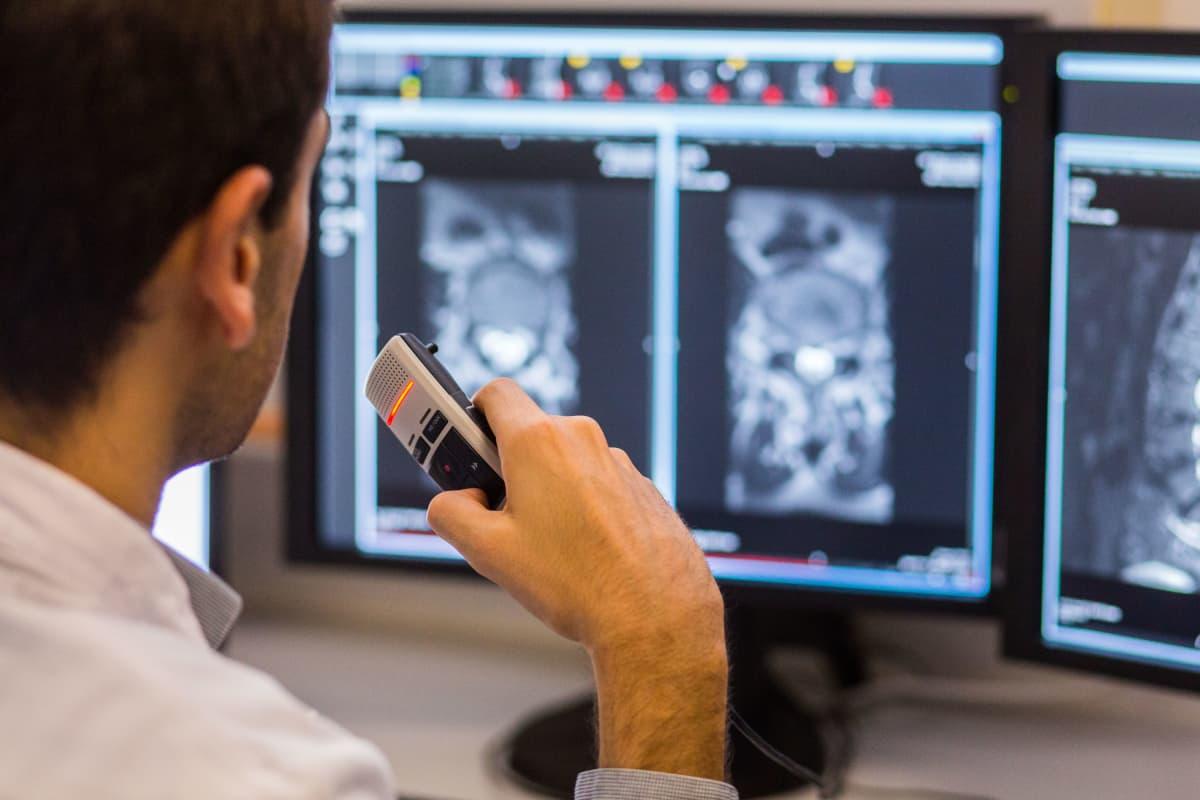 Läkare tittar på bilder från en MRI-undersökning och dikterar i en diktafon.
