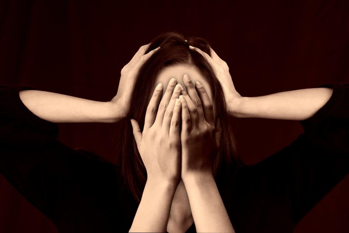 Nainen peittää kasvonsa ja korvansa neljällä käsivarrella