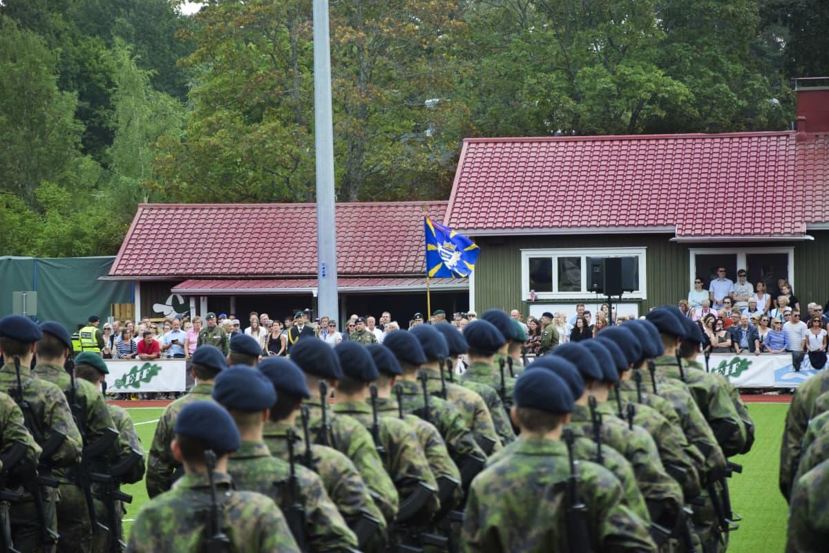 Militärparad med rekryter ute på en gräsplan. I bakgrunden pubilk.