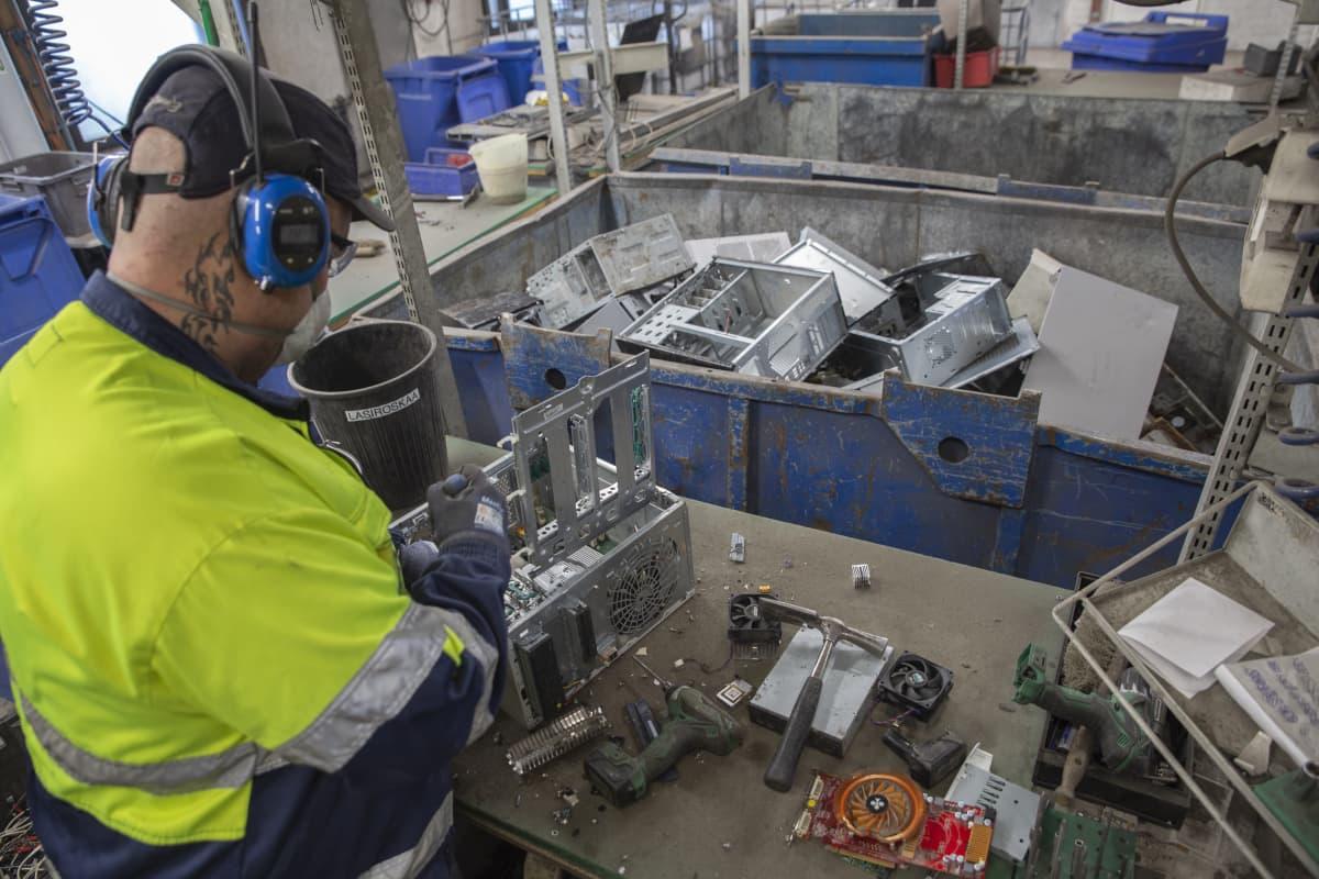 Työntekijä purkaa tietokonetta tehdashalliinsa.