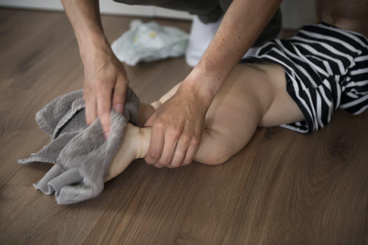 Vanhempi pyyhkii lapsen jalkoja.