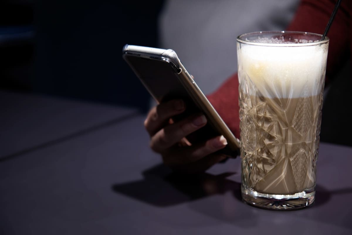Latte-kahvi, naisen käsi ja älypuhelin.