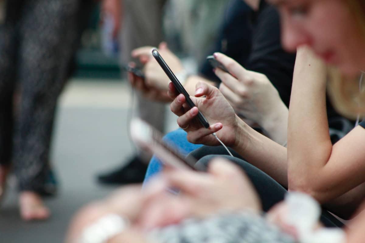 Unga ser på smarttelefoner på gatan.