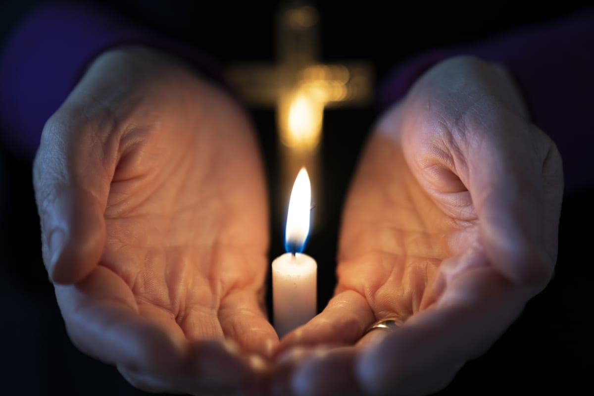 Kynttilä lähikuvassa käsien keskellä.