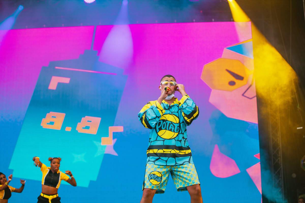 Siniseen kuviolliseen asuun puketunut portugalilaisartisti Bad Bunny laulaa mikkiin Ruisrockin Rantalavalla. Taustlla näkyy kaksi keltamustaan pukeutunutta taustatanssijaa ja värikkäät videovisuaalit.