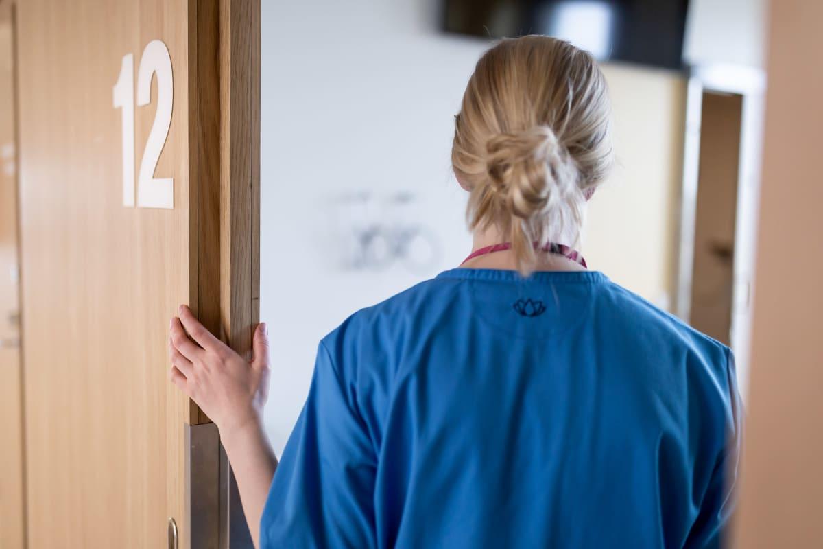 Sairaanhoitaja potilashuoneen ovella, Uusi lastensairaala, Helsinki, 8.7.2019.