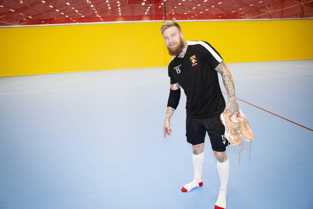 Teemu Tamminen KK osoittaa asentamiensa putkien sijaintia käsipallohallissa. Katse kameraan.
