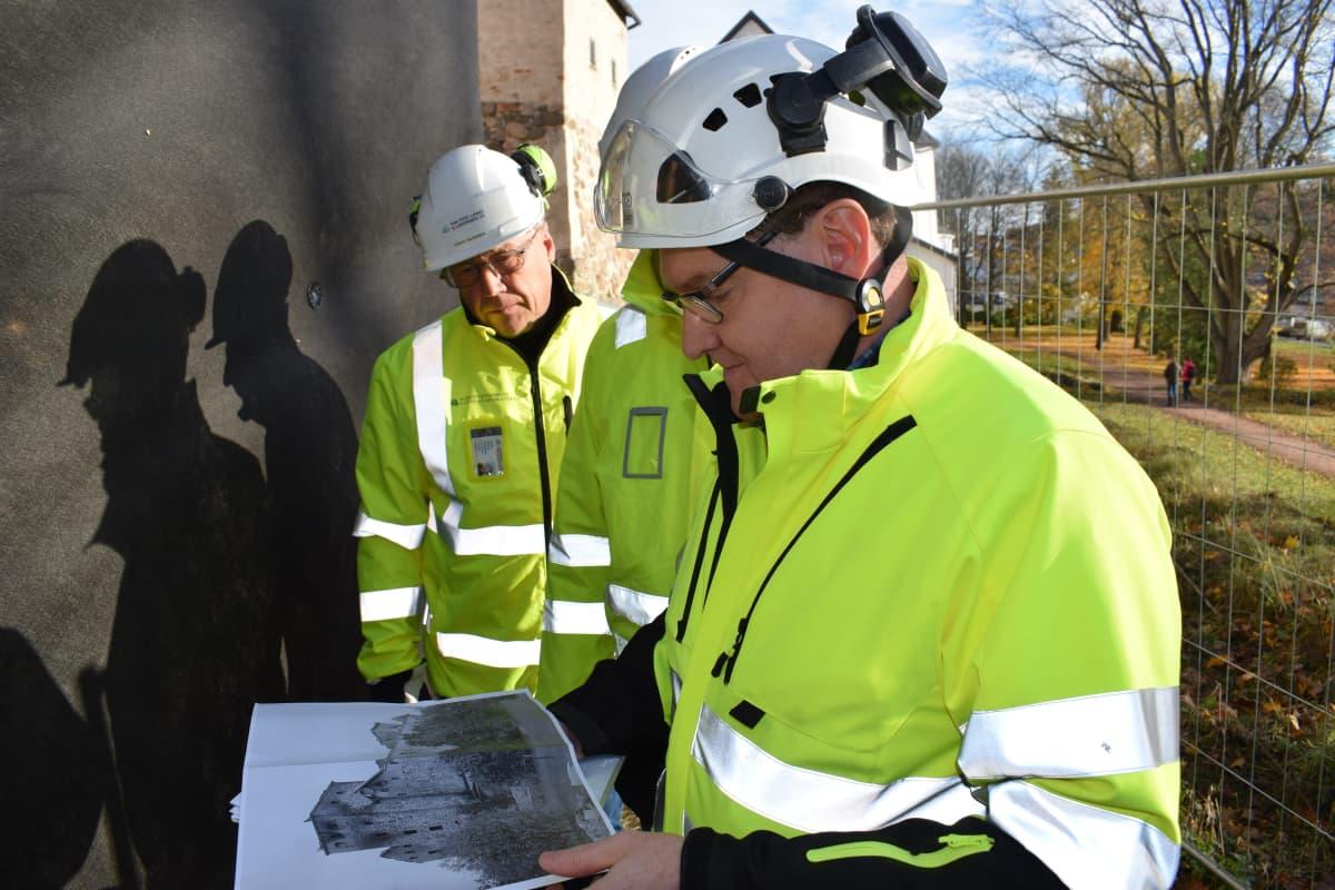 Miehet katsovat Turun linnan pommituksia esittelevää kuvaa