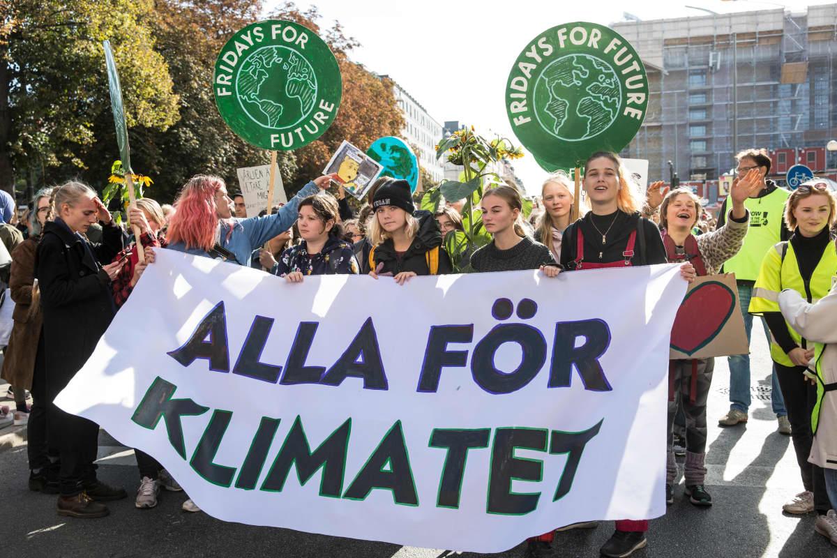 Tukholmassa nuoret osoittavat mieltään ilmaston puolesta. Kyltissä lukee Alla för klimatet.