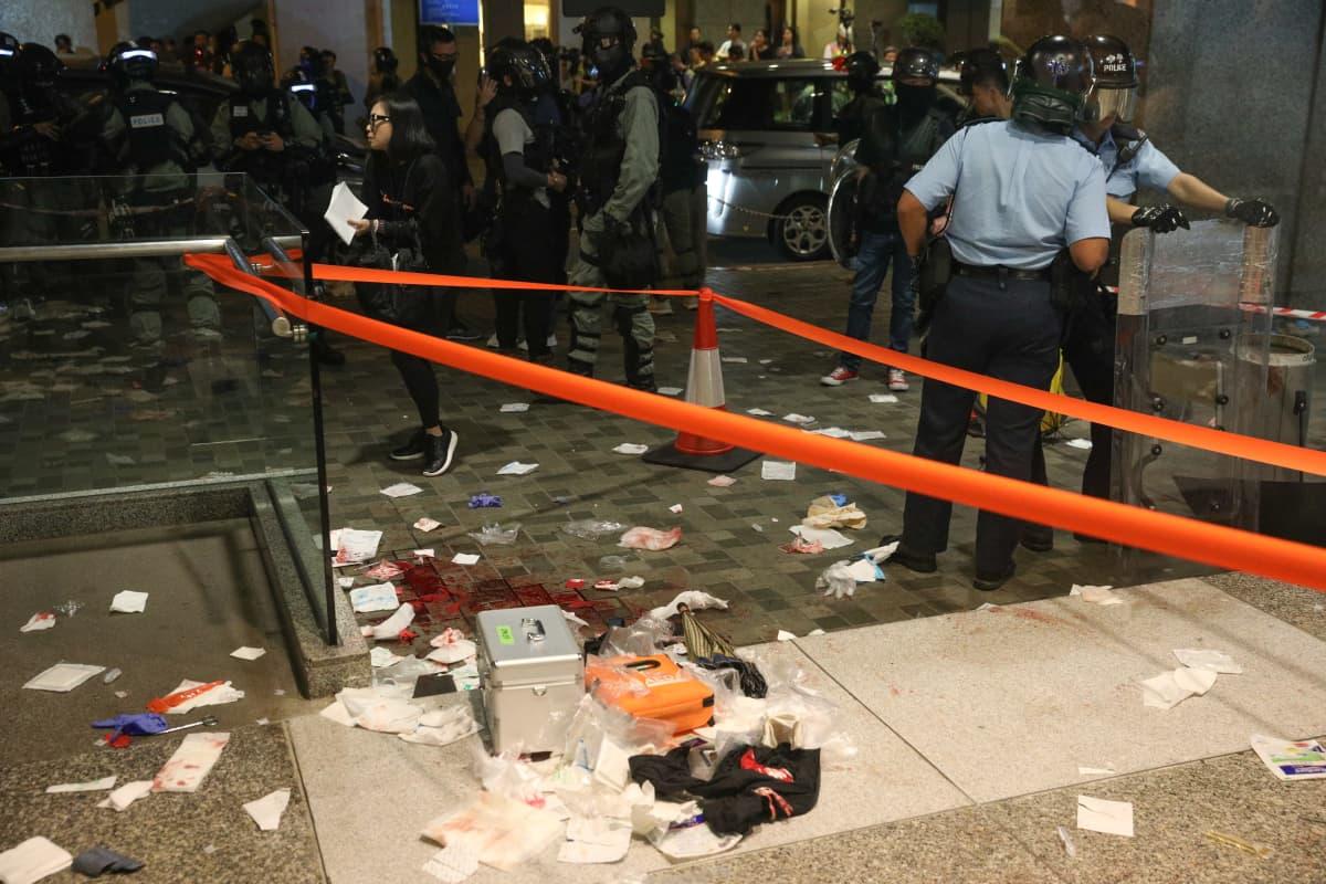 Verijälkiä ja ensiapuvälineitä lattialla. Taustalla poliiseja.