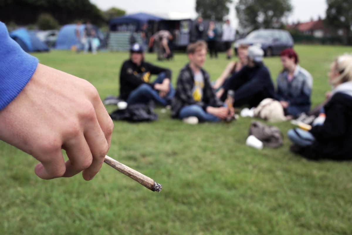 En hand håller i en joint i förgrunden. I bakgrunden syns suddigt ett gäng ungdomar som sitter i en ring på en gräsmatta.