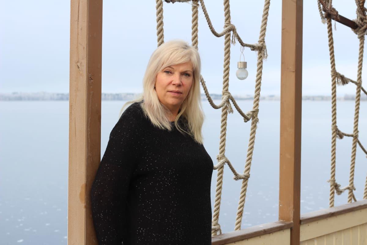 Natalia Alaspää terassilla, taustalla talvinen järvi.